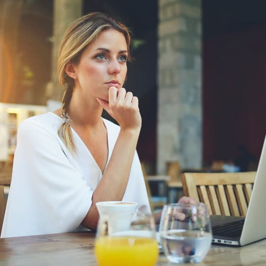 young woman thinking at laptop